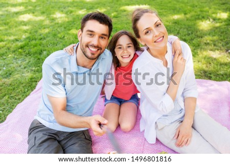 family, leisure and technology concept - happy mother, father and daughter having picnic and taking picture by selfie stick at summer park