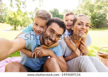 Photo of family, leisure and technology concept - happy mother, father and two little sons having picnic and taking selfie at summer park