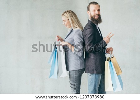 family leisure. happy smiling man showing victory sign. couple delighted with purchases they hold in bags.