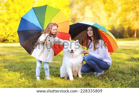 Family, leisure, weather and people concept - mother with child and dog walks with umbrellas outdoors in autumn day