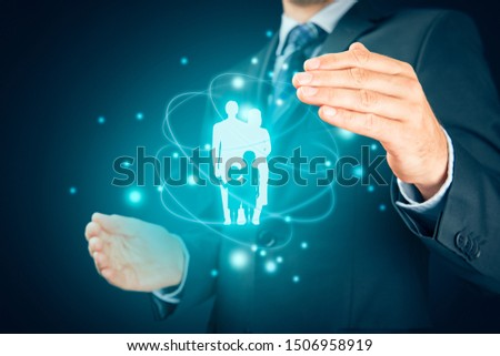 Family life insurance, services and supporting families concepts. Businessman with protective gesture and wooden figurines representing young insured family. #1506958919