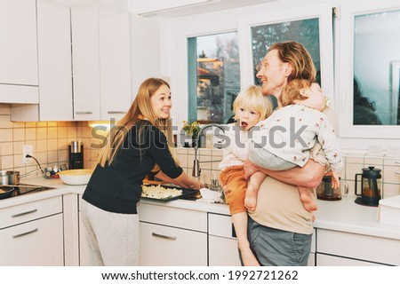 Family life, mother cooking dinner, father holding sleeping baby and excited toddler boy, happy parenthood