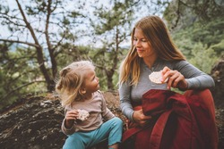 Family lifestyle mother and daughter child outdoor in forest on picnic eating rice cookies travel vacations together with kid