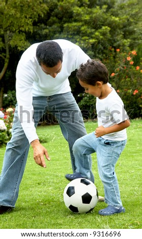 family lifestyle portrait of a dad with his son playing football
