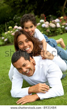 family lifestyle portrait of a mum and dad with their kid having fun outdoors