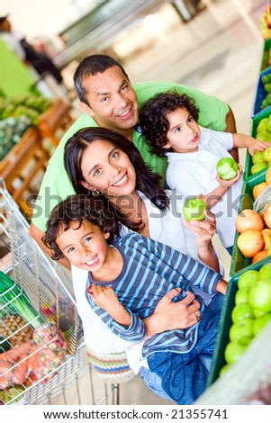 Family lifestyle portrait of a mum and dad with their two kids shopping in supermarket