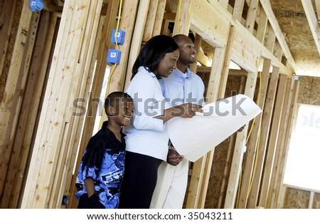 family looking at house blueprints