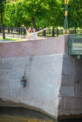Family looking at monument sculpture of Chizhik-Pyzhik small bird on Fontanka river, St. Petersburg, Russia