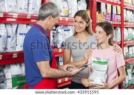 Family Looking At Salesman Using Digital Tablet In Pet Store