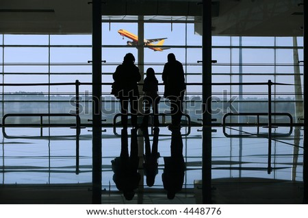 family looking to a airplane through the window in the airport