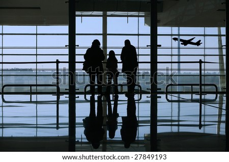 family looking to an airplane through the window in the airport