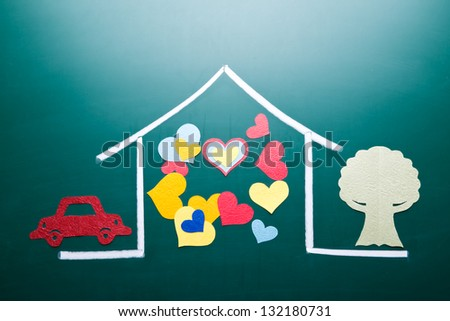 Family love concept, colorful heart shape in drawing house on blackboard. Paper cutting car and tree as decoration.