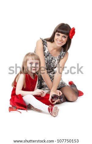 Family love of mother and daughter having fun embrace with happy laughter sitting on floor. A girl in a red dress, mother in fashionable clothes and shoes to sunglasses.