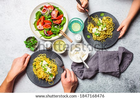 Family lunch table, top view. Peoples hands eating italian pasta with ricotta and fresh vegetables salad. Italian cuisine concept.
