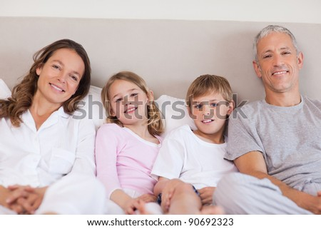 Family lying on a bed in while looking at the camera