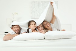 Family lying on bed in hotel room