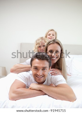 Family lying on each other on the bed