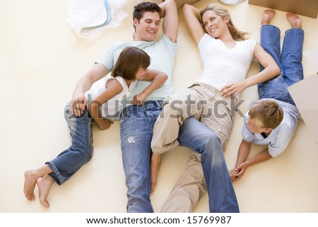 Family lying on floor by open boxes in new home smiling - stock photo
