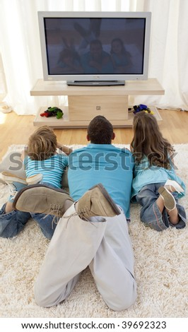 Family lying on floor in living-room watching television