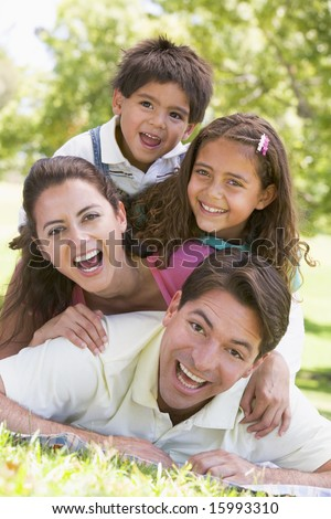 Family lying outdoors smiling