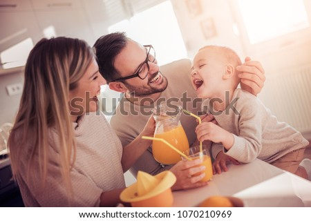 Family making juice in their kitchen.People,love,family,food and drink concept.