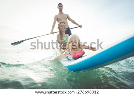 family making paddle surf in the ocean. concept about sport, healthy lifestyle and people