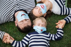 family - man, woman and boy in striped sweaters lie on grass, holding hands. They are wearing blue medical masks with funny smiles painted. Positive, mutual support during the covid-19 pandemic