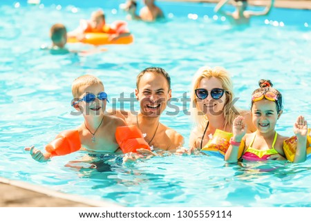 Family man woman boy girl in swimming pool, active leisure concept