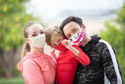 Family members embracing each other, smiling in the camera wearing cloth face masks. Many countries recommend citizens cover their faces during the world coronavirus covid-19 pandemic.
