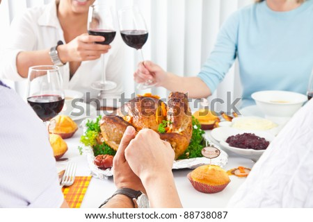 Family members giving thanks to God at festive table while holding each other by hands, close-up