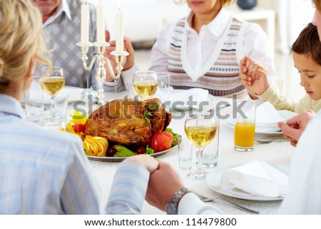 Family members giving thanks to God at festive table with roasted turkey on it