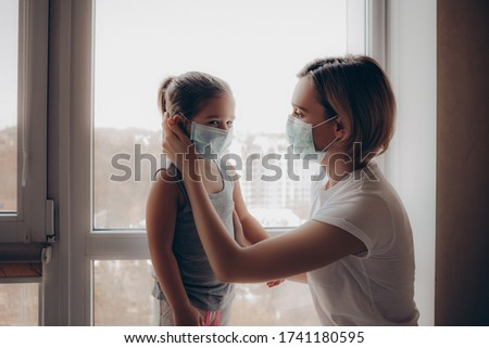 Family Mom and Daughter in Medical Mask. Young Woman and Child little girl sitting by the Window in Protective Masks against the Virus. Mom carefully corrects the mask on the face of the child