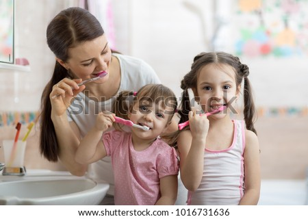 family mom and two daughters little girls brush their teeth