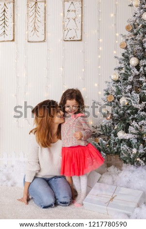 Family moments on Christmas eve, happy mother and daughter. Lovely moment with presents, lights  and decorated tree on backgrounds. #1217780590