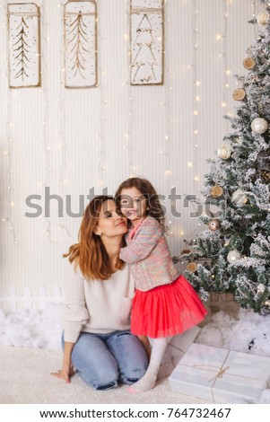 Family moments on Christmas eve, happy mother and daughter. Lovely moment with presents, lights  and decorated tree on backgrounds. #764732467