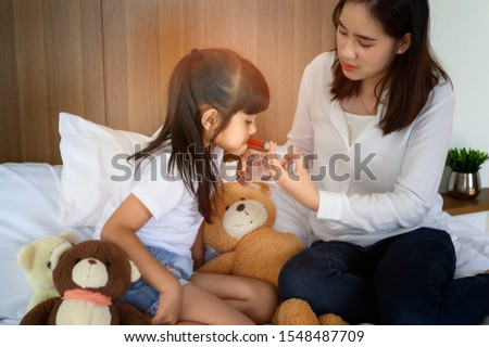 family mopther takes care of member sick in bedroom, taking liquid syrup drug potion to stop fever, worry and keep close looking for effective future