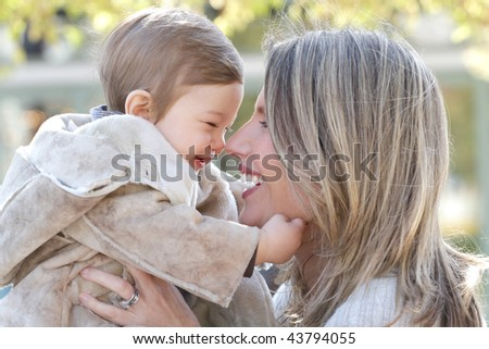 Family: mother and baby son having fun outdoors, city street setting, fall seasonal theme