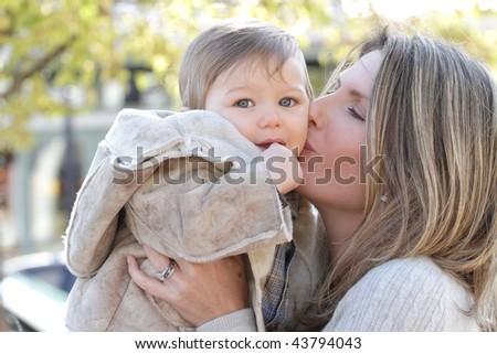 Family: mother and baby son having fun outdoors, city street setting, seasonal, fall theme