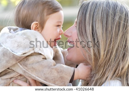 Family: mother and baby son outdoors, city street setting, seasonal, fall theme - stock photo