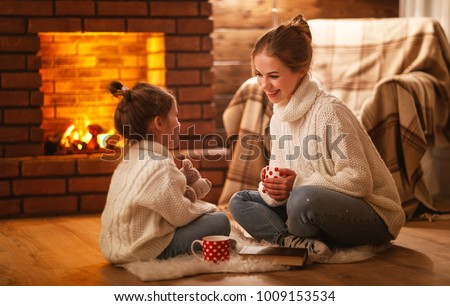 family mother and child daughter drinking tea and laughing on winter evening by fireplace #1009153534