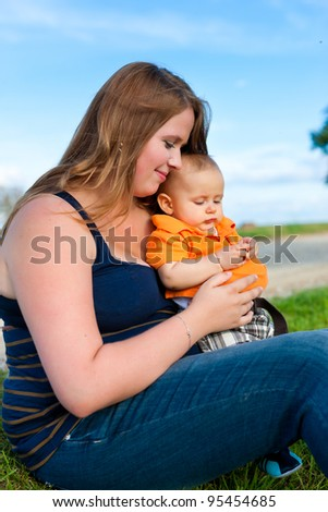 Family - mother and child playing in garden on a beautiful summer day