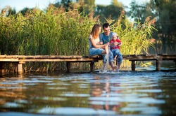 Family, mother, father and child playing and spending time with his young son in the summer the river or lake