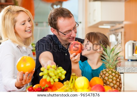 Family - mother, father and child - with lots of fruits for breakfast food, this is healthy nutrition