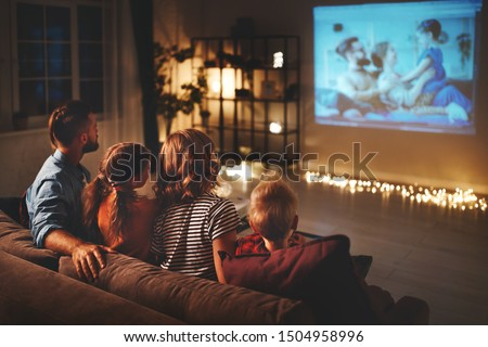 Photo of  family mother father and children watching projector, TV, movies with popcorn in the evening   at home