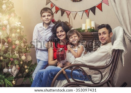 Family mother father and children with gifts in beautiful boxes in the Christmas interior