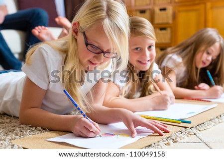 Family, mother, father and daughters are at home, the children coloring on the floor