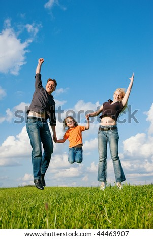 Family - mother, father, child - jumping high in the air on a green meadow at a late summer afternoon