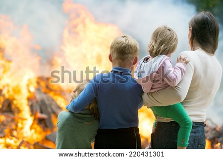 Family mother with children at burning house fire accident background stock photo