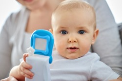 family, motherhood and people concept - close up of mother and little baby playing with toy phone at home