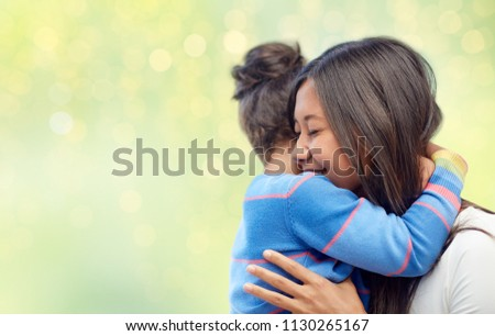 family, motherhood and people concept - happy mother and daughter hugging over green holidays lights background #1130265167